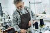 Fotografie Selektiver Fokus eines reifen männlichen Schneiders im Schürzenschnitt auf Nähmaschine in der Werkstatt