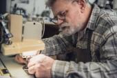 männliche Handtasche Handwerker Nähmaschine im Studio arbeiten konzentriert