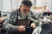 zralý muž Krejčí v brýle a Zástěra kožená stříhání nůžkami v dílně