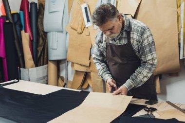 male handbag craftsman in apron working with cardboard at studio