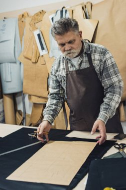 middle aged male leather handbag craftsman in apron working at studio