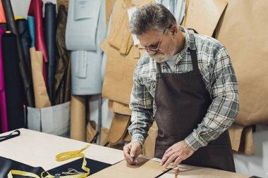 mature male leather handbag craftsman in apron and eyeglasses working at studio