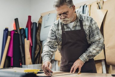 focused mature male leather handbag craftsman in apron and eyeglasses working at studio