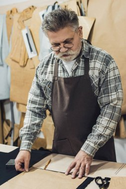 middle aged male leather handbag craftsman in apron and eyeglasses working at studio