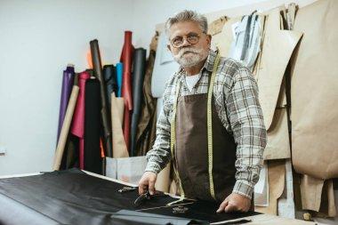 middle aged craftsman in apron and eyeglasses at workshop