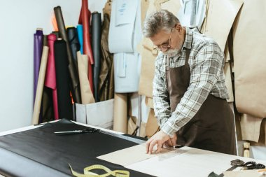 middle aged tailor in apron making measurements at workshop