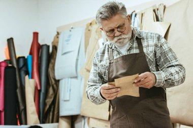 focused middle aged handbag craftsman in apron and eyeglasses working at studio