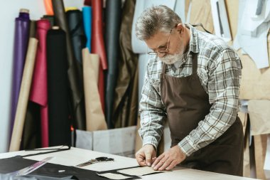 male middle aged handbag craftsman in apron and eyeglasses working at studio