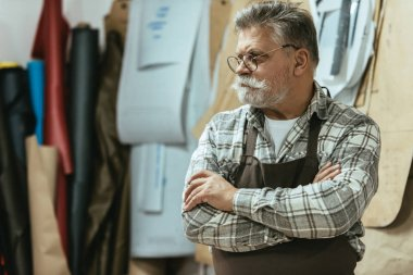 mature craftsman in apron and eyeglasses standing with crossed arms at studio