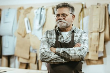 happy middle aged craftsman in apron and eyeglasses standing with crossed arms at studio
