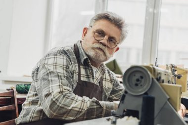 portrait of mature male tailor in apron and eyeglasses sitting near sewing machine at studio