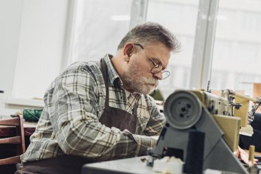 focused mature male tailor in apron and eyeglasses working on sewing machine at studio
