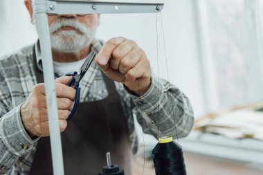 cropped image of middle aged tailor in apron cutting strings on sewing machine at workshop