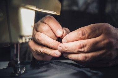 cropped image of male handbag craftsman sewing at studio