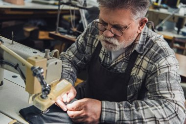 high angle view of male handbag craftsman working on sewing machine at studio
