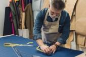 männliche mittleren Alter Handwerker in Schürze Messungen auf Stoff am workshop