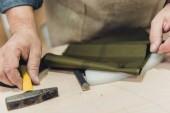 Fotografie ořízne obraz mužské kabelka řemeslník pracující s kladivem ve studiu