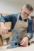 Fotografie zaměřil mužské kabelka řemeslník práci s nástrojem ve studiu