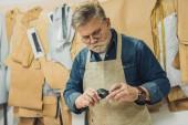 koncentrované středního věku mužského kabelka řemeslník zástěru a brýle pracovat s látkou ve studiu