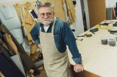 Fotografie erhöhte Ansicht glücklich mittleren gealterten männlichen Handwerker in Schürze posiert auf workshop