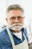 Fotografie Porträt von glücklich mittleren gealterten männlichen Handwerker in Schürze posiert auf Workshop hautnah
