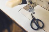 Fotografia messa a fuoco selettiva di macchina da cucire e forbici al workshop