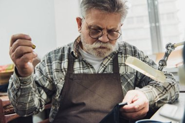 focused middle aged male tailor in eyeglasses and apron sewing at workshop