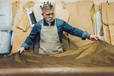 selective focus of middle aged male handbag craftsman putting fabric on working table at studio