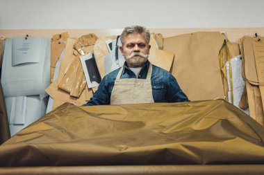 confident middle aged male handbag craftsman putting fabric on working table at studio