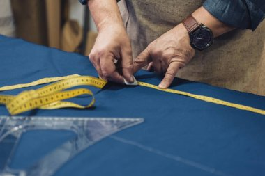 cropped image of male craftsman in apron making measurements on fabric at workshop