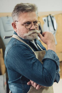 thoughtful middle aged male craftsman in apron looking away at workshop