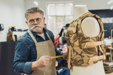 confident middle aged male tailor making measurements on military vest at workshop