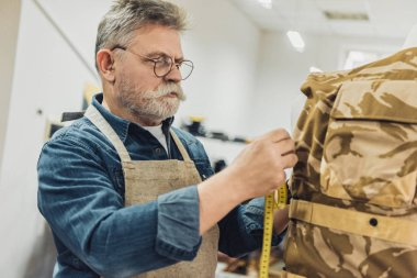 selective focus of middle aged male tailor making measurements on military vest at workshop