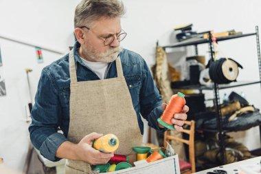 selective focus of middle aged craftsman choosing strings at workshop