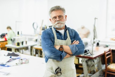 serious mature male craftsman in apron posing with crossed arms at workshop