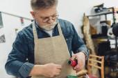 Fotografie ältere männliche Handwerker in Schürze mit Strings arbeiten im studio