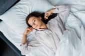pohled shora krásná brunetka žena v pyžamu, spí na posteli v noci