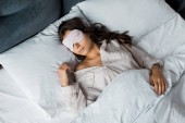 krásná mladá žena spí v oční maska v posteli