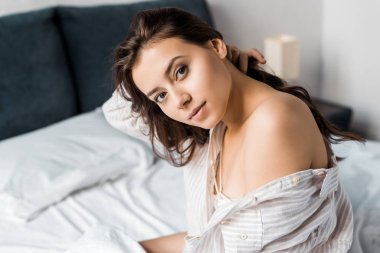 beautiful tender woman looking at camera and sitting on bed in the morning