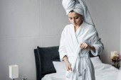 gyönyörű fiatal nő, fehér törülközőt fején viselt fürdőköpeny, a hálószobában