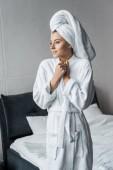 krásná zasněný žena v bílém županu a ručníku postavení v ložnici