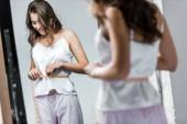 happy slim woman measuring her waistline against the mirror