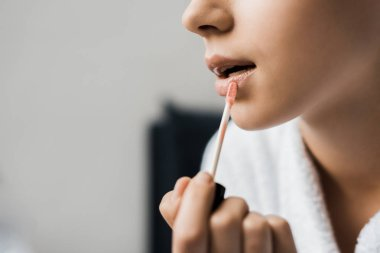 cropped view of girl applying lip gloss