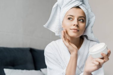 beautiful girl with towel on head applying cosmetic cream on face