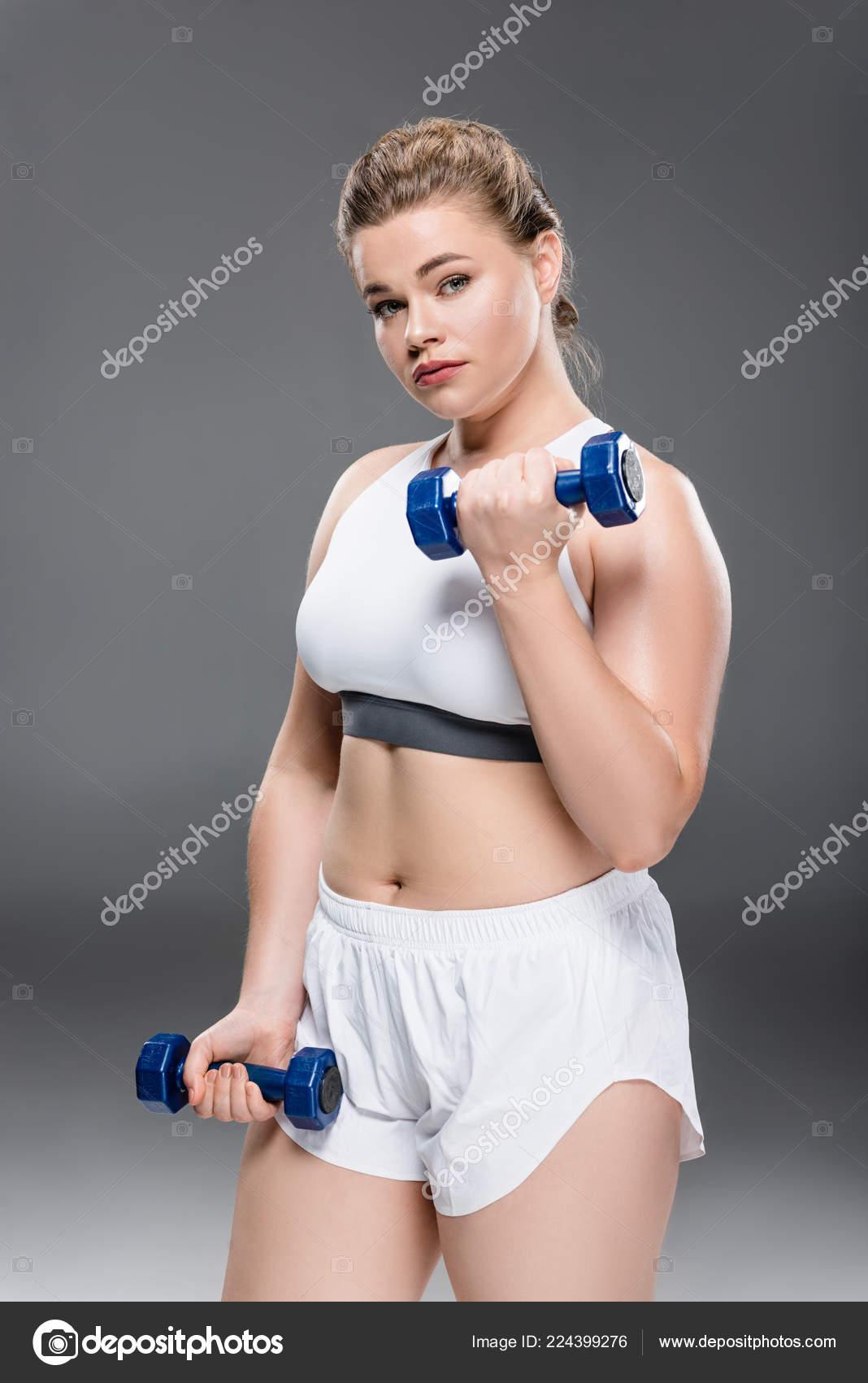 9d575a090dee Νεαρή Γυναίκα Υπέρβαροι Αθλητικά Ρούχα Άσκηση Βαράκια Και Κοιτάζοντας Την — Φωτογραφία  Αρχείου