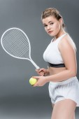 Photo young oversize woman with tennis racket and ball looking at camera on grey