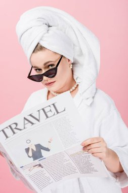 young oversize woman in bathrobe, sunglasses and towel on head reading travel newspaper and looking at camera isolated on pink