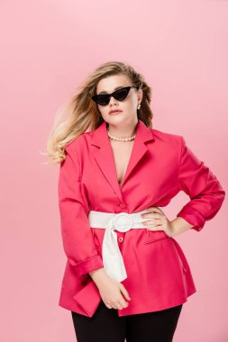 Attractive oversize girl in pink trench coat and sunglasses posing with hand on waist isolated on pink stock vector
