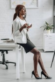 Fotografie african american adult businesswoman in white formal wear leaning on office desk, smiling and holding cup of coffee