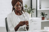 smiling african american adult businesswoman in white formal wear sitting at desk and using smartphone in office